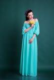 Mädchen mit Kranz von Blumen im blauen Modekleid Stockfotografie
