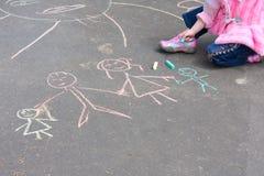 Mädchen mit Kreide auf Asphalt Stockbilder