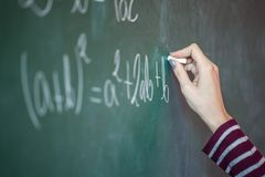 Mädchen mit Kreide in ihrer Hand löst ein mathematisches Problem auf stockfotos