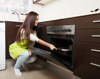 Mädchen mit Kuchen nahe dem Ofen stockbilder