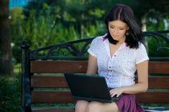 Mädchen mit Laptop im Park Lizenzfreie Stockbilder