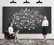 Mädchen mit Laptop und blonder Frau nahe Teamwork-Ikonen Lizenzfreie Stockfotografie