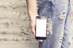 Mädchen mit leerem Bildschirm von Smartphone auf einem Ziegelsteinhintergrund Lizenzfreies Stockfoto