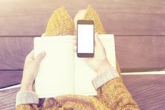 Mädchen mit leerem Handy und Tagebuch Stockfoto