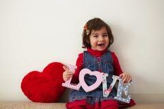 Mädchen mit Liebeszeichen und rotem Plüschherzen Lizenzfreies Stockbild