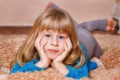 Mädchen mit lustigen Endstücken liegt auf dem Teppich stockfotografie