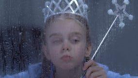 Mädchen mit magischer leidender Einsamkeit der Stabs- und Prinzessinkrone hinter regnerischem Fenster stock footage