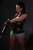 Mädchen mit Maschinengewehr auf dunklem Hintergrund Stockfoto