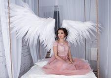 Mädchen mit offenem Engel beflügelt das Sitzen auf hängendem Bett Stockbild