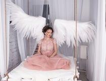 Mädchen mit offenem Engel beflügelt das Sitzen auf hängendem Bett Lizenzfreie Stockbilder