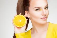 Mädchen mit Orange in ihrer Hand Lizenzfreie Stockfotos