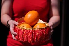 Mädchen mit orange Korb für Geschenke des Chinesischen Neujahrsfests Stockfotografie