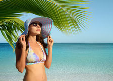 Mädchen mit Panama unter einer Palme auf dem Strand Stockbild