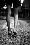 Mädchen mit Pantoffel gehend auf den Schotterweg allein im Freien lizenzfreie stockfotos