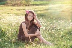 Mädchen mit Pfingstrose in ihrem Haar, das auf dem Feld sitzt und betrachtet stockfotos