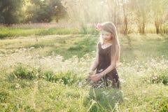 Mädchen mit Pfingstrose in ihrem Haar, das auf dem Feld sitzt und Florida zupft stockbild
