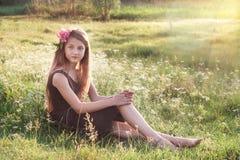 Mädchen mit Pfingstrose in ihrem Haar, das auf dem Feld sitzt und int schaut stockbild