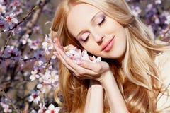 Mädchen mit Pfirsichblumen in den Händen Stockbilder