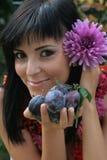 Mädchen mit Pflaumen und Blumen Lizenzfreie Stockfotos