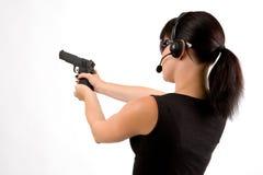 Mädchen mit Pistole und Kopfhörern. Stockbilder