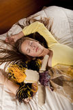 Mädchen mit Puppe auf dem Bett Stockbilder