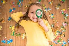 Mädchen mit Puzzlespiel und Lupe Lizenzfreie Stockbilder