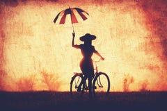 Mädchen mit Regenschirm auf einem Fahrrad Lizenzfreie Stockfotos