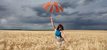 Mädchen mit Regenschirm am Feld. Lizenzfreie Stockfotos