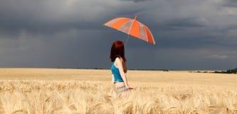 Mädchen mit Regenschirm am Feld. im Sturm lizenzfreie stockbilder