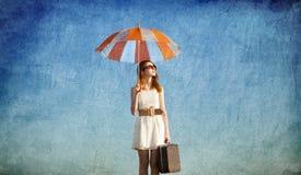 Mädchen mit Regenschirm und Koffer Stockbild