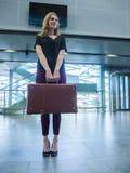 Mädchen mit Retro- Koffer der Weinlese im Flughafenabfertigungsgebäude Stockfotografie