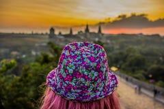 Mädchen mit rosa Hut und dem rosa Haar zurück zu Kamera auf Sonnenunterganghintergrund lizenzfreie stockfotografie