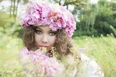 Mädchen mit rosafarbenem Pfingstrosenkranz Stockbilder