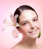 Mädchen mit rosafarbener Blume auf Haar Lizenzfreie Stockfotos