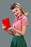 Mädchen mit rotem Buch auf grauem Hintergrund Stockbilder