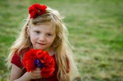 Mädchen mit roten Blumen Stockbilder