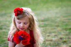 Mädchen mit roten Blumen Stockfotografie