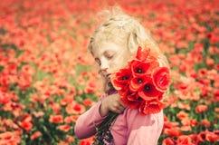 Mädchen mit roten Blumen gegen roten Blumenhintergrund Stockbild