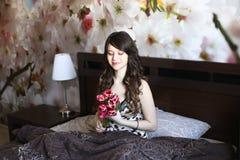 Mädchen mit roten Blumen im Bett Stockfoto