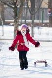 Mädchen mit Schlittenrest am Winterschnee Lizenzfreies Stockfoto