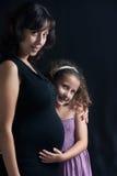 Mädchen mit schwangerer Mama lizenzfreie stockbilder