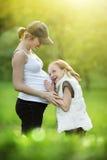 Mädchen mit schwangerer Mutter Stockfotografie