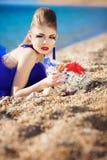 Mädchen mit Seashells auf dem Strand Stockfotografie