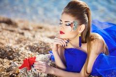 Mädchen mit Seashells auf dem Strand Stockbild