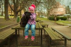 Mädchen mit seinem schwarzen Schnauzerhund auf einer Holzbank Lizenzfreies Stockbild