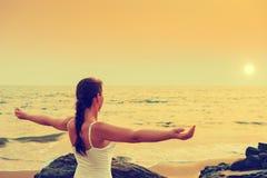 Mädchen mit seinen Händen verbreitete auseinander bei Sonnenuntergang durch das Meer stockfoto