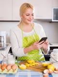 Mädchen mit Smartphone an der Küche Lizenzfreie Stockfotos