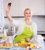 Mädchen mit Smartphone an der Küche Stockbilder