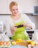Mädchen mit Smartphone an der Küche Stockfoto