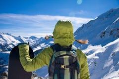 Mädchen mit Snowboard agaist die Berge stockfotografie